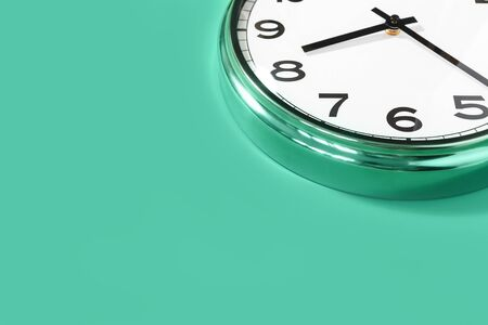 Part of analogue plain wall clock on trendy pastel green background. eight thirty oclock. Close up with copy space, time management concept and opening closure time