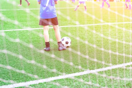 Child with soccer ball at football grounds watching the game, view through goal net with copy space, football or sports and tournament at school concept with light glow