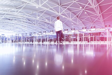 One child boy with bag alone at the airport checkin desk waiting area with glowing light. Travel flights delay and luggage allowance for family vacation trips concept with copy space