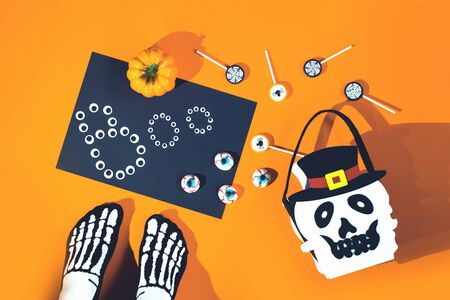 Happy Halloween candy bucket face of Jack O Lantern with lollypops with spiders and nets on orange background and bloody eyes sweets and sceleton feet. Flat lay trick or treat with copy space 写真素材