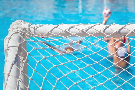 Children paly water polo with ball in swimming pool. View through goal net selective focus. Summer fun sports with copy space