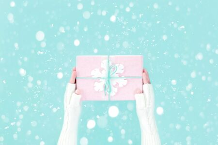 Hands in warm white knitted mittens holding winter pink gift box with snowflake on pastel blue packground. Festive Merry Christmas Boxing Day or New Year season's greeting card with copy space