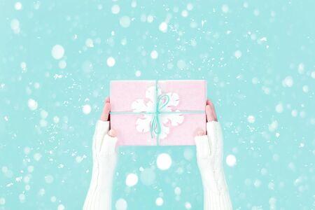 Manos en guantes de punto blanco cálido con caja de regalo rosa de invierno con copo de nieve en azul pastel packground. Feliz Navidad festiva Boxing Day o tarjeta de felicitación de la temporada de año nuevo con espacio de copia