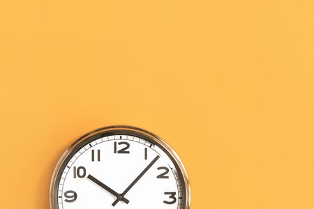 Time concept. Part of white wall clock on trendy pastel orange background. Close up with copy space, time management or school concept and summer or winter daylight saving time change Stockfoto