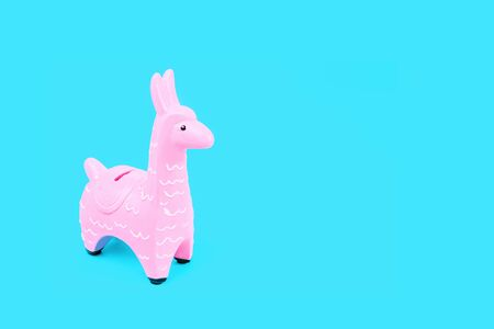 Pink zine type toy alpaca llama on blue background close up, coin money bank. Creative and fun trendy collage of funky animal saving for travel concept with copy space