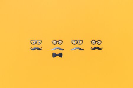 Four faces with mustaches and glasses for Movember on yellow orange. Barber or mens health concept. Fathers day flat lay with copy space Stock Photo