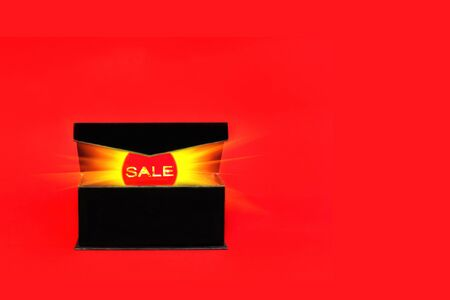 Red sale tag with glowing light out of black box on red background. Black friday or cyber monday sale banner with copy space