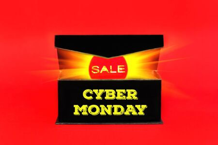 Red sale tag with glowing light out of black box on red background. Cyber Monday words sign with copy space