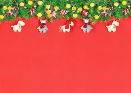 Merry Christmas tree garland of cool red cute handmade soft toys pendant ornaments and stars with lights on red background. Christmas or new year celebration festive greeting card border Stok Fotoğraf