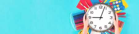 Clock over office school sets of multicolored bright stationery on pastel blue background in kids hands. Flat lay banner. back to school creative education craft design concept. school start time. Stok Fotoğraf