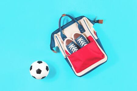 School backpack with trainers and soccer ball. Flat lay on trendy light blue background with copy space. Education sports classes or kids activity