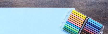 Assorted multicolored pastel markers office or school set of stationery on baby blue background on wooden desk. Flat lay copy space. back to school creative design education craft concept banner.