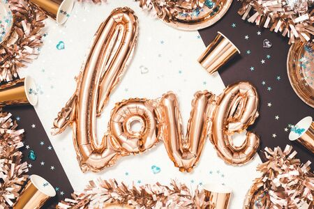 Gold monochrome metallic love word foil balloon on party table with shining paper glasses plates and tinsel with heart and star confetti. flat lay Valentines day or wedding hen party concept Stock Photo
