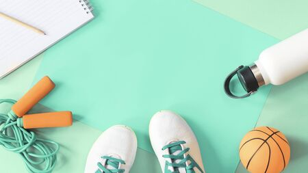 Sports healthy education concept with football cleats, jumping skipping rope, ball and water bottle and a notepad. Flat lay with copy space on tender pastel green background