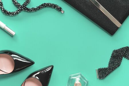 Black female patent high heel shoes and shiny clutch with luxury stone bracelet and necklace with cosmetics on green background. Party and beauty shopping blogger concept flat lay border copy space