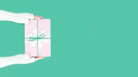 Hands in warm white knitted mittens holding winter pink gift box with snowflake on pastel green packground. Festive Merry Christmas Boxing Day or New Year seasons greeting card with copy space banner Stok Fotoğraf