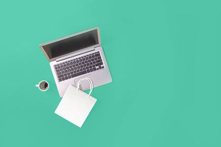 Laptop with gift shopping bag on trending green background with coffee cup. Online internet shopping concept flat lay with copy space. Black Friday Cyber Monday Stok Fotoğraf