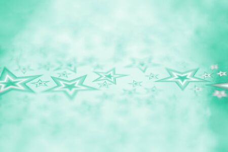 Festive shiny metal foil sheet in trendy green color with stars sequin and bokeh. Christmas or New Year background or backdrop. Selective focus Stok Fotoğraf