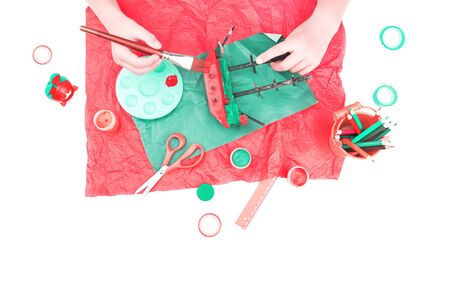 Kids hands painting a wooden ship in red and biscay green. flat lay top view isolated on white. Back to school or education art, crafts and creativity concept Stok Fotoğraf
