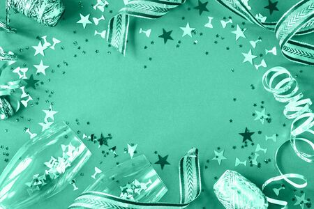 Bright glitter biscay green and neo mint and festive confetti and ribbons on trendy background with two sparkling wine flutes. flat lay border for celebration or greeting card with copy space Stok Fotoğraf