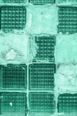 Old grunge broken green glass tile blocks background sealed with cement. Textured background in monochromatic trendy biscay green shades