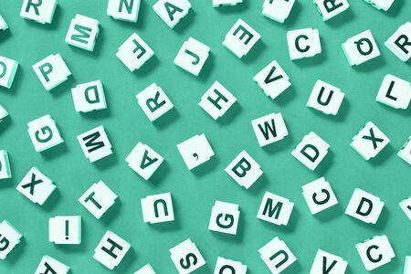 letter cubes scattered on monochromatic green, dictionary or dyslexia reading difficulty and disorder visual and auditory memory or test concept. Education and neurology with copy space