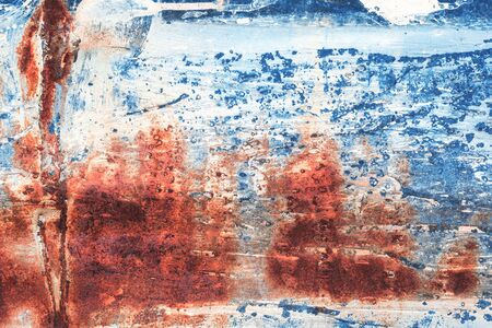 Old grungy cracked weathered wall paint peeling off rusted metal sheet. Textured blue and red background for posters and bloggers