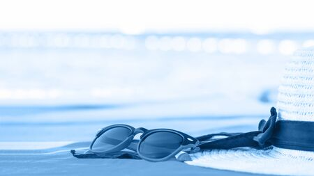 White Summer hat with trending blue sunglasses at seaside. Top view, minimal monochrome concept over a blue background with copy space banner