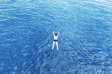 Caucasian boy swimming in the vast open blue pure sea waters. Relaxing summer or exotic travel and vacation destination scenic. Copy space