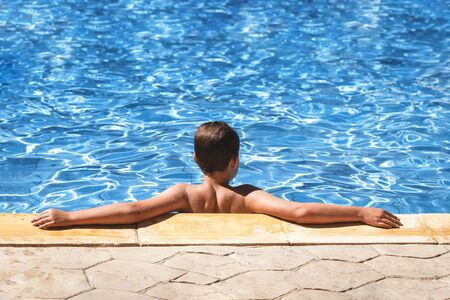 Tanned wet caucasian boy enjoying the sun in the swimming pool with blue water. Droplets on his back and hands. Relaxing summer or exotic vacation. Copy space