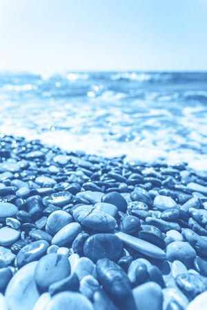 Wet pebble stones and sea water in beautiful morning light. Monochrome blue color. Closeup, travel and vacation destination concept, meditation, mindfulness and classic clear mind banner or backdrop