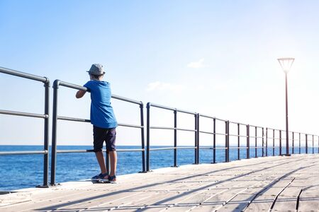Candid view of child in blue tshirt on a long wooden pier at seaside looking at blue water. Lots of air and copy space. Travel and tourism Stok Fotoğraf