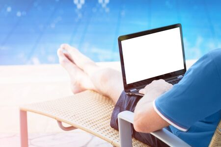Rear view of man in blue polo with a laptop and blank white mock up screen in sun lounge chair at poolside. Flexible remote working, travelling, advert and copy space Stok Fotoğraf