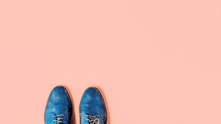 Pair of shiny gradient blue shoes on trendy peach quartz color background. Minimalistic flat lay with copy space. Hipster blog advert or shoe fashion or repair service concept banner