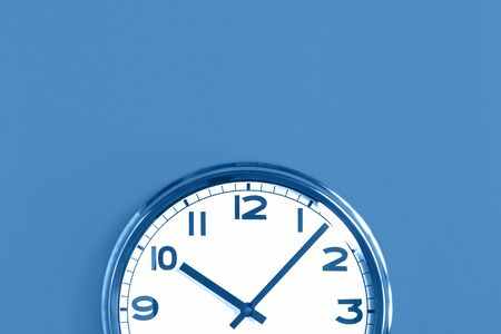 Top of big plain wall clock on trending pastel blue background. Ten o'clock. Close up with copy space, time management or school concept and summer or winter time change, opening hours
