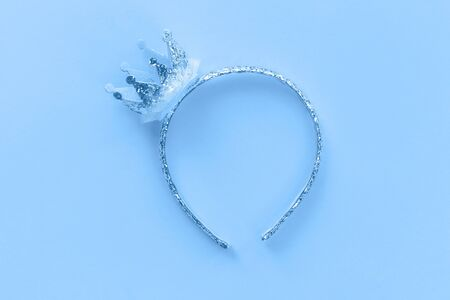 Blue and silver glitter princess crown headband for girls on pastel light blue background. Festive birthday party or performance. Feminine or girlie minimal flat lay with copy space