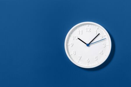 Big white plain wall clock on trending dark blue background. Ten oclock. Close up with copy space, time management or school concept and summer standard or winter time change, opening hours.