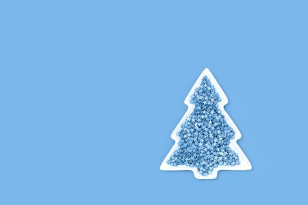Blue nonpareils cake candy sprinkles in white Christmas tree shaped bowl on pastel blue trending background in flat lay with copy space. Party celebration or bakery concept