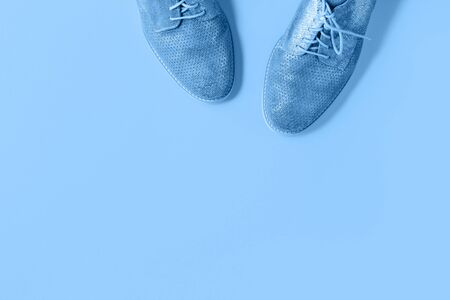 Pair of gradient blue suede shoes on trending monochrome color background. Minimalistic flat lay with copy space. Hipster blog advert or shoe fashion or repair service concept banner Stok Fotoğraf