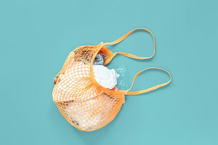 Orange Crochet net bag stuffed with old plastic bags on blue background, creative flat lay for environment friendly zero waste and palstic free ecological life concept. Copy space