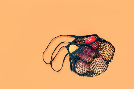 Black crochet net eco bag stuffed with fruits and vegetables on orange background, creative flat lay for environment friendly zero waste and plastic free ecological life concept. Copy space Stok Fotoğraf