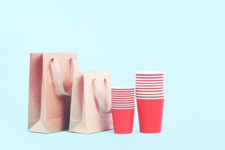 Red paper cups rows and buff paper shopping bags on light blue background with copy space, beyond plastic free concept