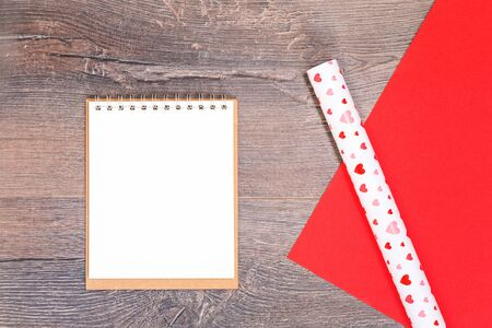 Heart gift wrapping paper and a notepad on wooden desk. Flat lay with copy space for Valentines Day and romance love letter and celebration concept