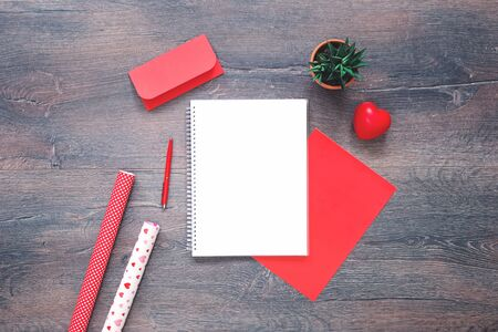red heart with red stationery envelope notepad with gift wrapping paper and cactus pot on wooden desk. Flat lay with copy space for Mothers or Valentines Day and romance love letter or message concept