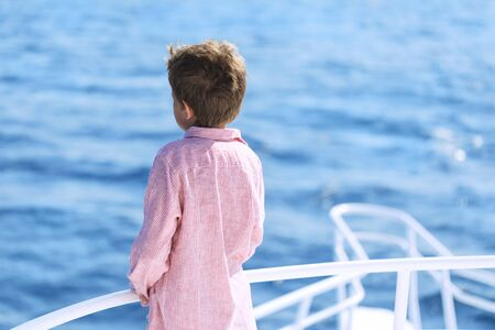 One caucasian child boy enjoying a boat sea trip. Standing at the stern and looking at the vast blue sea ocean waters. Travel destination and family dreams vacation concept