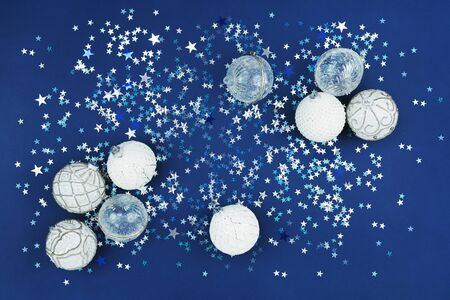 Christmas white baubles collection with sparks on festive blue confetti glitter background. Merry Christmas or Happy new year card or banner flat lay concept in trending color with copy space