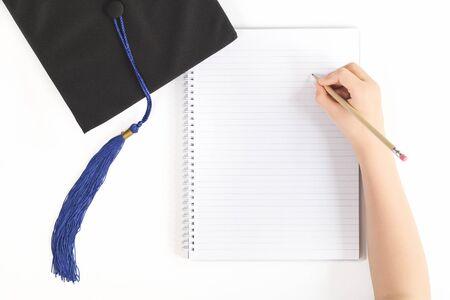 Gorro de graduación negro con cuaderno y una escritura a mano en un cuaderno. Conocimiento y aprendizaje de la educación. Redacción de tesis y pruebas con espacio de copia.