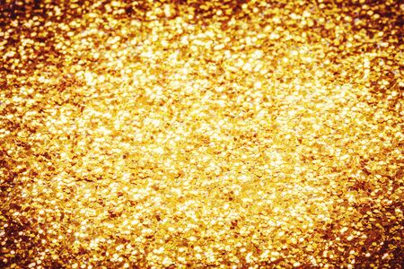Golden festive sparkling glitter confetti with blurred bokeh textured background. Luxury celebration themed backdrop with copy space. Selective focus