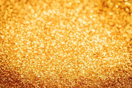 Confettis scintillants festifs dorés avec fond texturé bokeh flou. Toile de fond sur le thème de la célébration de luxe avec espace de copie. Mise au point sélective