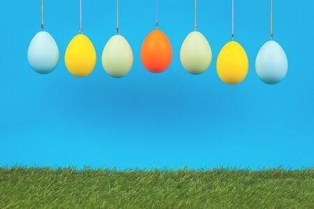 Easter greeting card with dyed eggs garland with blue background, grass and eggs with copy space and copy space